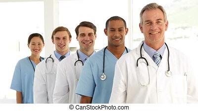 équipe, regard, appareil photo, traversant armes, monde médical