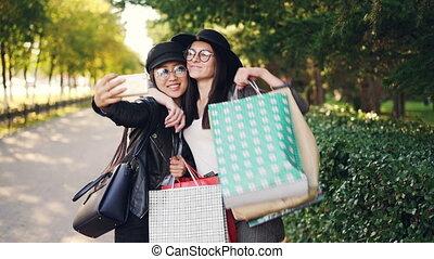achats, smartphone, achats, tenue, sacs, amis, selfie, moderne, ensoleillé, excité, automne, prendre, femme, utilisation, jeunesse, day., technologie, concept.