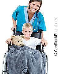 adorable, peu, beau, docteur féminin, porter, fauteuil roulant, hôpital, garçon