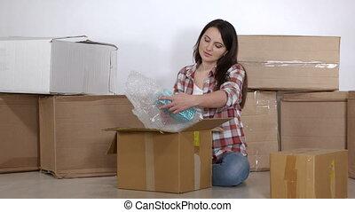appartement, séance, plancher, boîtes, femme, en mouvement, nouveau, déballe, carton