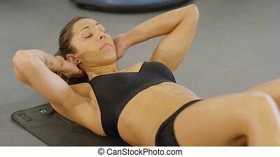 assied-augmente, femme, plancher, gymnase, concentré, fitness