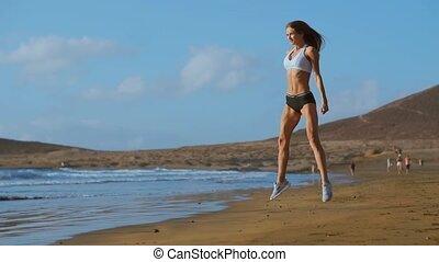 athlétique, s'accroupit, exercice, engagé, femme, sports., outdoors., femme, sunset., extérieur, fitness, sportive, fonctionnement, porter, vêtements de sport, dehors, plage, jeune