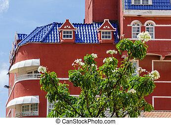 bâtiment, arbre fleurissant, arrière-plan rouge