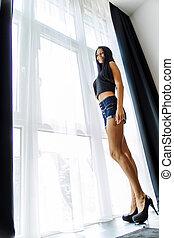 beau, élevé, femme, jeune regarder, fenêtre, talons, dehors