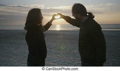 beau, coeur, alors, couple, leur, forme, tenant mains, confection, plage, levers de soleil, baisers