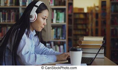 beau, concentré, café, project., étudiant, fonctionnement, séance, copybook, bureau, jeune, bibliothèque, ordinateur portable, écouteurs, école, femelle asiatique, dactylographie, girl, écriture, boire