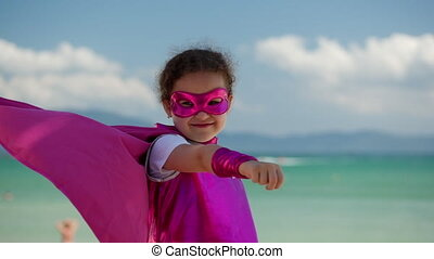 beau, concept, poing, sends, nuages, déguisement, mer, girl, bleu, peu, superhero, habillé, ciel, manteau, heureux, arrière-plan rose, jeux, forward., hero., masque, childhood.