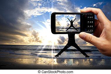 beau, mobile, téléphone appareil-photo, sauter, heureux, plage, levers de soleil, homme