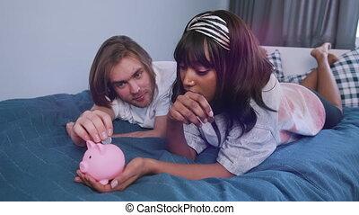 bed., mensonge, banque, couple, économies, concept, quoique, richesse, multiracial, pièces, mettre, jeune, porcin, famille