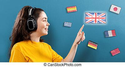 bleu, elle, jour, flags., jeune, ligne, écouteurs, anglaise, doigt, learning., langue, portrait, flag., concept, fond, porter, sourire, pointu, différent, femme