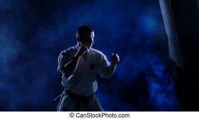 bleu, mouvement, sac sable, karaté pratiquant, arrière-plan., lent, silhouette, homme
