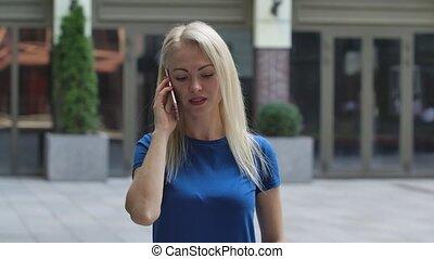 bleu, rue., jeune, dehors, portrait, smartphone., fin, haut., blond, elle, chemisier, femme, motion., conversation, charmer, fond, lent