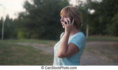 blond, slo-mo, beau, parc vert, été, téléphone, conversation, femme