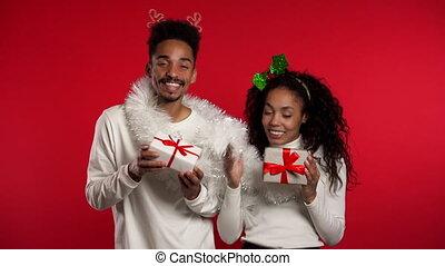 boîte, cadeau, studio., isolé, jeune, fête, concept., présente, fond, bonheur, décorations noël, rouges, américain, danse, couple, africaine, nouvel an