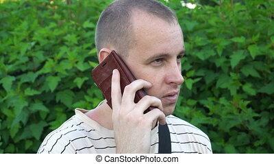 buissons, conversation, jeune, téléphone, rue, arrière-plan vert, homme