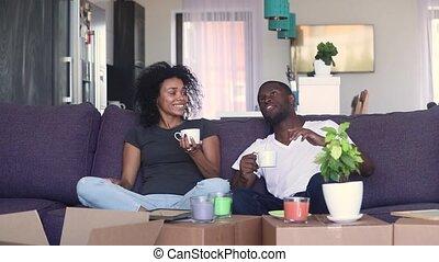 café, couple, africaine, boîtes, nouvelle maison, boire, déballage, heureux