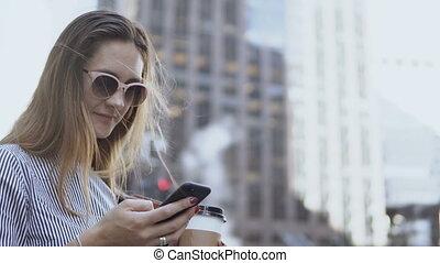 café, lunettes soleil, avoirs entourent, femme affaires, jeune, rue, pendant, break., portrait, utilisation, smartphone