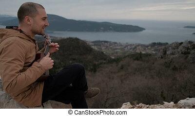 chante, jeux, ukulele, hawaien, jeune, colline, assied, outdoors., homme