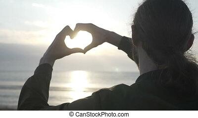 coeur, lent, silhouette, regarder, jeune, long, haut, cheveux, forme, sien, coucher soleil, mains, confection, fin, plage, mouvement, homme