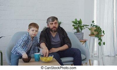 concentré, peu, football, manger, famille, regardant télé, concept., père, applaudissement, fils, élevé, célébrer, cinq, victoire, allumette, sport, snacks., maison, heureux
