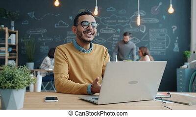 confection, afro-américain, portrait, heureux, utilisation, vidéo, ordinateur portable, travail, appeler, homme affaires