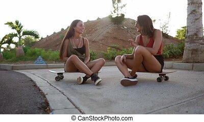 conseils, filles, light., longboard, parc, deux, plaisanteries, patin, coucher soleil, rire, asseoir, sourire, conversation, amis, parler