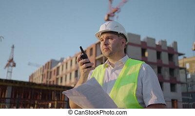 contremaître, gilet, poursuite, quelques-uns, constructeurs, ingénieurs, talkie-walkie, expert, construction, prise vue., surprenant, sunlight., site, casque, conversation, radio, constructeurs, debout, bâtiment, parler, utilisation