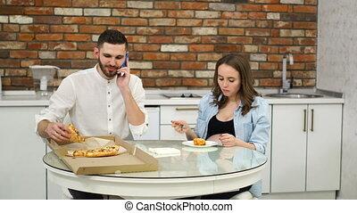 conversation, femme mange, pregnant, kitchen., leur, dîner, maison, pendant, pizza, téléphone, homme