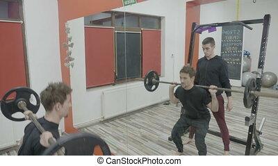 corps, entraîneur, sien, aide, s'accroupit, personnel, gymnase, travail, muscles, poids, mâle, levage, dehors