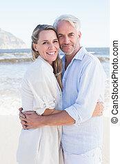 couple étreindre, regarder, appareil photo, plage, heureux