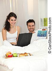 couple, ordinateur portable, lit