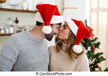 couple, santa, chapeaux, arbre noël, heureux, baisers