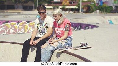 couple, skateboarders, jeune, bavarder, séance