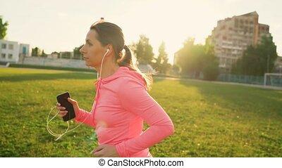 courses, smartphone, écouteurs, femme, par, stade, coucher soleil
