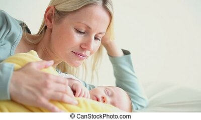 couverture jaune, tenant bébé, femme