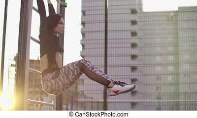 crise, projection, femme, station, augmentations, sain, coup, abdominal, six-pack., jambe, motion:, coucher soleil, pendre, extérieur, exécuter, ville, fitness, vrai, franc, lent, fort, park.