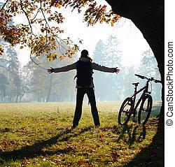 cycliste, debout, femme, tendu, parc, embrasser, freedom., vitalité, extérieur, mains, excité