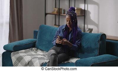 dame, séance, afro-américain, téléphone, divan, messages, cellule, femme, envoi, bavarder, messager, noir