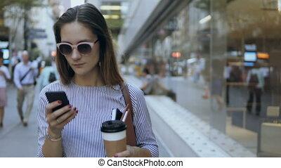 debout, bâtiment, café, bureau, tasse, femme affaires, jeune, portrait, utilisation, smartphone., heureux