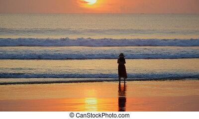 debout, belle femme, silhouette, chapeau, coucher soleil, ocean., vagues, apprécier, plage