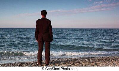 debout, cailloux, homme, plage, complet