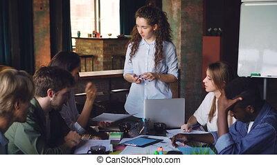 debout, collègues, partage, joli, elle, meeting., idées, jeune regarder, conversation, pendant, femme, quoique, collègues, papiers, table, business