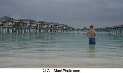 debout, eau, maldives., villas., océan, vient, devant, plage blanche, sablonneux, homme