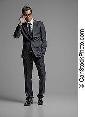 debout, entiers, lunettes soleil, suit., jeunes hommes, isolé, gris, confiant, longueur, hommes affaires