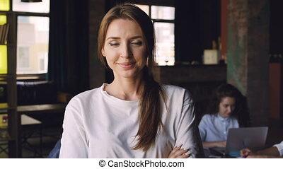 debout, femme, bureau occupé, elle, ouvrier, jeune, quoique, regarder, arrière-plan., lieu travail, appareil photo, joli, portrait, sourire, collègues, fonctionnement