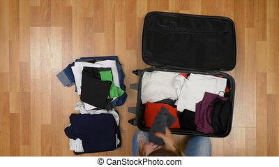 debout, femme, plancher, sommet bois, vue, séduisant, valise, déballage, vêtements