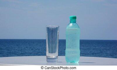 debout, fond, arrosez verre, table, bouteille, froid, mer