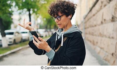 debout, gadgets, femme, bouclé, earphones., communication, concept., internet, jeune, cheveux, conversation, smartphone, ligne, dehors, utilisation, amis, lunettes