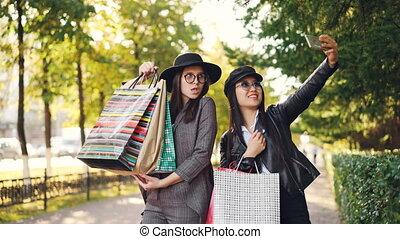 debout, sacs, smartphone, heureux, porter, selfie, filles, jeunes femmes, papier, prendre, dehors, utilisation, trottoir, clothing., amis, désinvolte, posing.