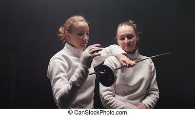 deux, appareil photo, poser, autour de, épée, quand, femmes, escrimeurs, jeune, faire idiot